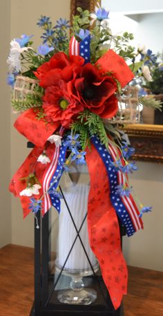 America the Beautiful lantern swag reflects the colors of our beautiful country.  The main flower in this arrangement is a poppy.  It also has a full collection of miniature flowers and greenery.  A burlap ribbon has been added in the back to tie on your lantern.  Our lantern shown for demonstration is 22.5 tall, but any lantern will work. $40.00