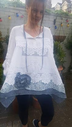 This is a lagenlook style top tunic made from a white linen shirt for the bodice and a stunning vintage lace crochet white tablecloth for the skirt. It has a sweet rolled neck with a picot lace trim and a daisy trim sits at the bustline. The hem is a cotton blue and white pattern