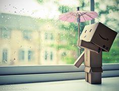 Cute little box man watching the rain