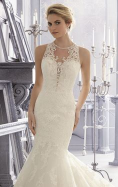 Be swept away in timeless romance in Bridal by Mori Lee 2683. This charming wedding gown features a high scoop neckline. The fitted bodice with is embellished with beads flatters your gorgeous silhouette. This piece is adorned with embroidery and alencon lace all over that will give you a classic style. A mermaid flared skirt with train completes a captivating look. This style is available in either 61, 58, or 55 inches, subject to availability.