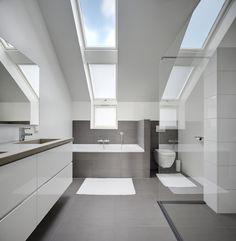 Ruime, trendy badkamer met wit- en grijstinten. En voor uw gemak onderhoudsvriendelijke dakramen. #FAKRO #dakraam #daglicht
