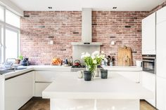 Handleless white kitchen. Bare brick wall. Kid & Coe | The Brahmsstraat Residence | Amsterdam