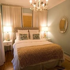 relaxing, pretty bedroom - pale blue walls, cream or winter-white linens/drapes, camel carpet, white night stands, brown/cream geometric print button-tufted headboard
