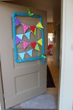Spray painted an old, plastic mirror frame (Color: Lagoon, by Rustoleum) and hung a store-bought pennant banner on it. Great rainbow party decor!