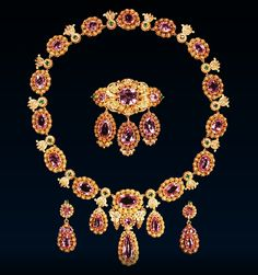 Pink Topaz Parure Circa 1820 – 30. The matte and burnished cannetille gold parure comprises a pair of top and drop earrings, a necklace and a Sévigné brooch set with pink topazes, with emeralds at each of the ends of the brooch and set in leaf and grape motifs  between the graduated oval pink topaz clusters in the necklace. The centre cluster, flanked by bunches of grapes is hung with a smaller cluster terminating in a drop similar to those in the earrings and brooch.