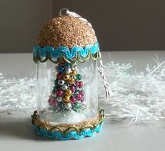"Vintage Retro 60s Style Pill Bottle Christmas Tree Scene Terrarium Ornament - This little pretty was made from a clear bottle, new bottle brush tree, vintage beads, burnished gold and clear glitter, and new trims. The hanger is bakers twine. It measures approximately 1-3/4"" diam. x 2-2/3"" tall."