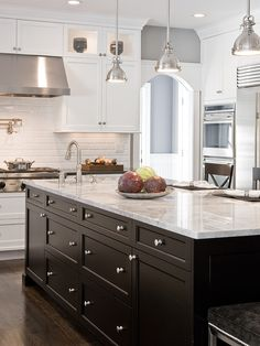 Love the slightly modern yet classic feel of this kitchen. love the silver nail head trim on the upholstered stools in the bottom right corner. The combination of cool grey marble with white subway tile back splash, dark ebony island, white cabinets with very simple wood trim detail, and silver fixtures, give the space a sophisticated, contemporary yet classic look.