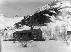 FAKf-100187.142685 Kan dette bilde vere teke i det område Standalhytta står i dag. Eg synes at eg kjenner igjen den karakteristiske fjelltoppen (Kolåstind) i himmelsjå? (Informant: Arnvid Hatlebrekke.) Fjellhytte, bygning, snø, fjelltopp, landskap, Ørsta, Standalshytta | 1905 - 1920