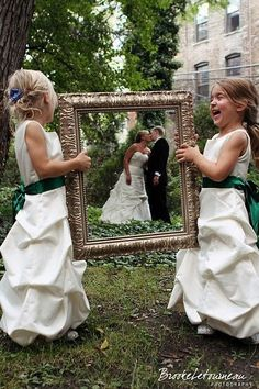 Great wedding photo idea - little flower girls holding a frame around the bride and groom