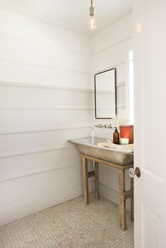 Cottage powder room features horizontal trim moldings on walls framing metal mirror over rustic washstand topped with antique Dutch grain bucket sink paired with wall-mounted faucet illuminated by single filament light pendant atop reclaimed marble tiled floor.