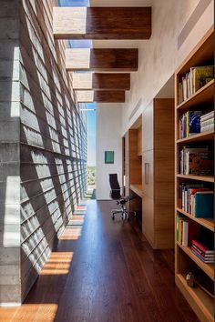 There's a home office in this hallway, with a built-in wood bookshelf and a desk.