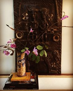 Vignette from my home. Wooden carved screen from Mali in the background. Tenmoku pottery from Malaysia and orchid tree flowers. Kachnar flowers, African art, Asian decor, African decor, Indian home, global decor. Floral vignette