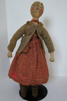 """An amazing survivor is this early painted face doll with rosy cheeks and bright blue eyes. She has on her original dress with a dear little hand stitched pocket, an added old sweater that covers sleeves that are mostly gone. I would call this doll a Roger Bacon type. I think she would have made him smile. She is 18"""" tall, firmly stuffed, rolled nose and the sweetest look. She doesn't bend easily but can sit. She is a real treasure but not for everyone. Circa 1880."""