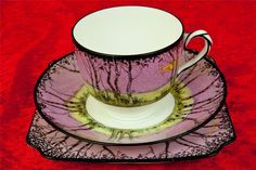 Doulton deco: unnamed tea trio, Rd 718210, c1920s. Pink colourway - stylised landscape in pink twilight setting with yellow moon, and black twisted handle feature, highlights and trim. Rare colourway, especially with square side plate; variant of purple (H5287) and blue (H5288) colourways.