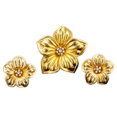Flower clip-on earrings and brooch made by Van Cleef & Arpels and featuring softly contoured petals of gold and centers of round diamonds.