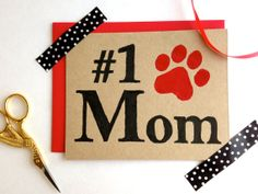 """Ecofriendly Mother's Day Card Percentage to Animal Rescue by bestinshore, $5.00 Blank inside for your personal message. Back: logo stamp. Size: A2 4.25"""" x 5.5"""" Carefully packaged in a clear sleeve and gift wrapped to ensure a safe arrival. All products are block-printed by hand. #1 Mom, Dog Mom, Cat Mom, linocut, Kraft Card, Pawprint, Rustic, Pet, Black and Red Collect one now {and re-pin!}: www.etsy.com/listing/184429772/eco-friendly-mothers-day-card-percentage?ref=listing-shop-header-1"""