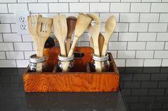 old wood en tool box holding wooden spoons in mason jars