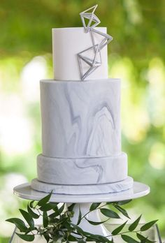 Pretty prisms top off this three-tiered marble wedding cake. Created by Cake by Nicole.