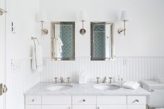 Three Thomas O'Brien Bryant Sconces illuminate side-by-side polished nickel framed inset medicine cabinets positioned over a white beadboard backsplash lined with a white dual washstand fitted with flat front cabinets adorned with nickel hardware topped with honed carrera marble framing his and her sinks and polished nickel cross-handle faucets.