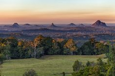 Glasshouse Mountains from Mary Cairncross Park, near Maleny. The highrise buildings of Brisbane can just be seen on the horizon in the middle of the frame. Visit Australia, Queensland Australia, Australia Travel, Sunshine Coast, Costa Do Sol, Glasshouse Mountains, Semarang, Glass House, Stunning View