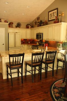 Pretty Traditional White Kitchen With Bar Chairs And Sloped Ceiling