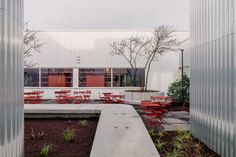 Aluminium cladding continues into a central landscaped courtyard that houses plants, as well as bright red furniture and a concrete bridge that connects two parts of the office. Interior Color Schemes, Colour Schemes, Aluminium Cladding, Architectural Materials, Corrugated Metal, Acoustic Panels, Through The Window, Urban Landscape, Blue Walls