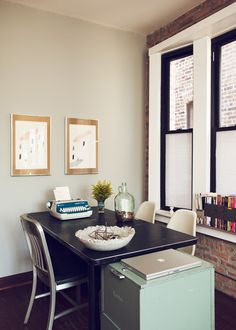 Love the old filing cabinet, chairs and typewriter.      Benjamin Moore's Sea Haze with the crisp white moulding and black window frames