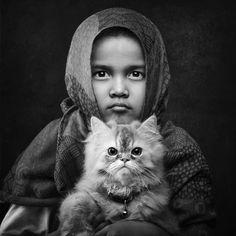 """""""Fina es la más pequeña de mis dos hijas. Solía temerle a los gatos, por lo que decidimos adoptar dos. Queríamos que aprendiera a vivir con los gatos, cómo cuidar de ellos y tratarlos como parte de la familia, para de ese modo ayudarla a superar su miedo. iAhora podemos decir con orgullo que lo hizo! Siete meses han pasado y hoy Fina y los gatos son los mejores amigos"""". Foto: Arief Siswandhono, Indonesia."""