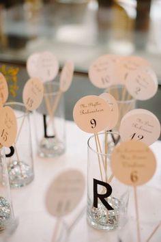 a modern take on the seating chart - names on a stick placed in corresponding letter glasses    Photography by dlweddings.com  Read more - http://www.stylemepretty.com/2013/09/06/new-york-city-wedding-from-divine-light-photography/