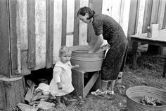 Farmer's wife washing clothes and watching son at same time, near Morganza, Louisiana, 1938: Russell Lee