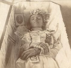 Young woman in her coffin, surrounded by pictures of her loved ones.