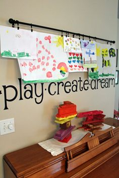 cute way to display children's artwork - curtain rod, hooks, and wall word decals saying play, create, and dream.