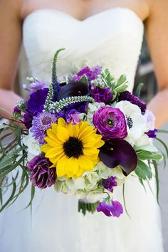 Love this mostly purple & white bouquet with sunflower focal point!  ~ we ❤…