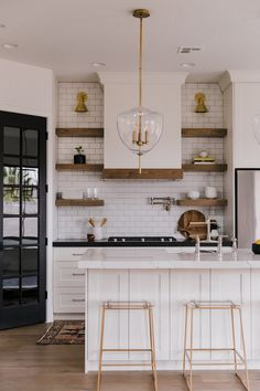 This kitchen really shows how to mix metals, wood tones, white and a pop of contrast. Love it all!
