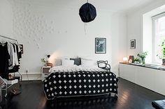 Chambre dans maison de maître avec placards sur mesure à proximité immédiate des fenêtres et agencement du lit en parallèle de celles-ci.