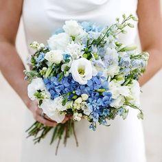 Beautiful Wedding Bouquet Featuring: White Lisianthus + Buds, White Freesia, White Hyacinth, White Snowberry, Blue Delphinium, Blue Hydrangea, Blue Tweedia, Greenery Foliage