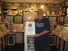 Dennis Schrader holding the Guinness Book of World Records' certifying his 4,400 baseball collection is the world's largest.
