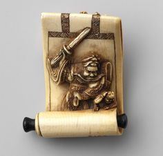 Netsuke: Hanging scroll with image of Shôki and demons, 19th century  Japanese  Ivory  H. 1 3/4 in. (4.5 cm), W. 1 7/16 in. (3.7 cm), D. 9/16 in. (1.5 cm)  Gift of Mrs. Russell Sage, 1910 (10.211.513)
