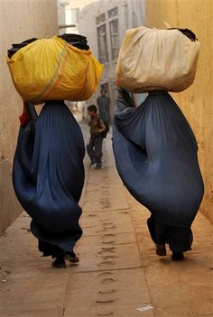 Afghan women clad in burqas carry second hand clothes to wash before trying to sell them in Kabul, Afghanistan, on Tuesday, Oct. 13, 2009. (AP Photo/Farzana Wahidy