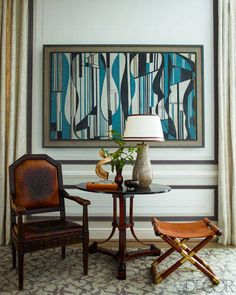 In this living room, a painting conceals the home's television. Installing a cabinet and television into the wall and covering it with a moveable piece of art allows the focus to change when needed.