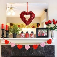 Red-and-Pink Valentine's Mantel  Red pillar candles, roses, and jars of candy complement a store-bought heart wreath on this simple and colorful Valentine's Day mantel. To craft the heart garland, Erin (thesunnysideupblog.com) glued twisted squares of red and pink tissue paper onto cardstock hearts. A family photo adds a nice personal touch.
