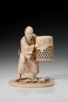 A superb Japanese ivory okimono figure of a farmer lifting a wooden cage and releasing his chicken and chicks. Signed. Meiji period Height: 5.75 in / 14.61 cm Width: 4.5 in / 11.43 cm Depth: 4 in / 10.16 cm