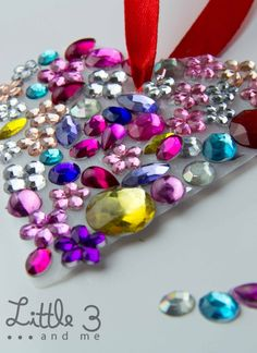 Jeweled Heart Suncatcher. How cute would this be hanging in a little girls room or on her door. AND she can make it herself! Glue plastic jewels onto heart-shaped tagboard!