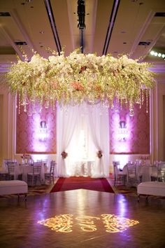 Ceremony deigned with a floral chandelier of orchids, larkspur and dangling crystals.