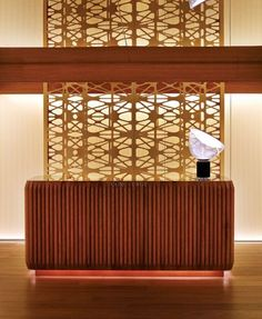Reception Desk: Varnished Wood   The reception desk here features an emphasis on strong horizontal lines with thin strips of timber glued onto a marble or metallic surface.