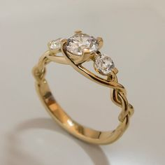 A handmade 14K gold braided ring set with three clear diamonds.    This ring is set with clear diamonds but can be set with any stones you choose,
