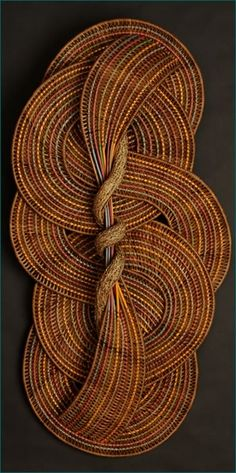 """Circles and Curves  (2011)  H 55"""" W 27"""" D 6""""  A twisted piece of bittersweet vine lies at the center of this weaving which has no beginning and no end. Woven with smoke colored reeds and spokes of different pastel colors, this large wall sculpture is both an intriguing piece and a stunning example of Tina Puckett's basket artistry. Circles and Curves can be hung either horizontally or vertically."""