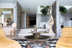 Creative. Malibu home. Sculptural furniture and art add visual interest. Ficus tree in atrium.  Designer: Kelly Wearstler.