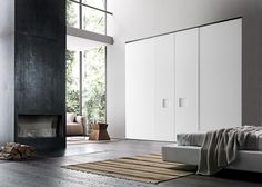 Wardrobe with Alibi coplanar sliding doors in matt bianco candido lacquer with a large square insert in the same finish.__ Armadio con anta complanare Alibi laccato opaco bianco candido con inserto quadrato grande laccato opaco bianco candido.