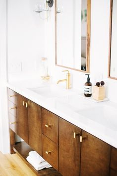 Bathroom with brass accents, and a wooden double vanity